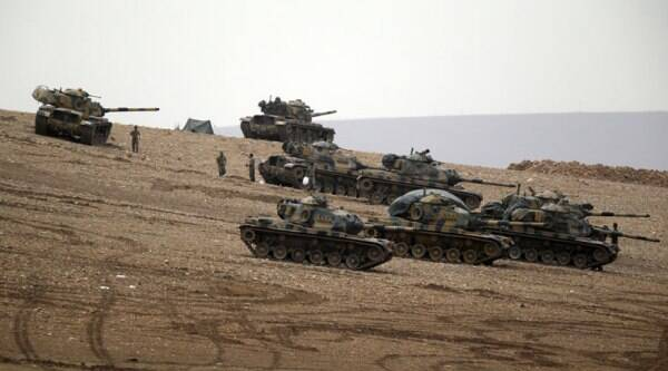 Turkish soldiers hold their positions with their tanks on a hilltop on the outskirts of Suruc, at the Turkey-Syria border, overlooking Kobani, Syria, during fighting between Syrian Kurds and the militants of Islamic State group, Sunday, Oct. 12, 2014. (Source: AP)