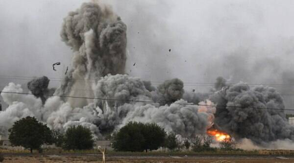 Thick smoke, debris and fire rise following an airstrike by the US-led coalition in Kobani, Syria as fighting intensified between Syrian Kurds and the militants of Islamic State group, as seen from Mursitpinar on the outskirts of Suruc, at the Turkey-Syria border, Sunday, Oct. 12, 2014. (Source: AP)