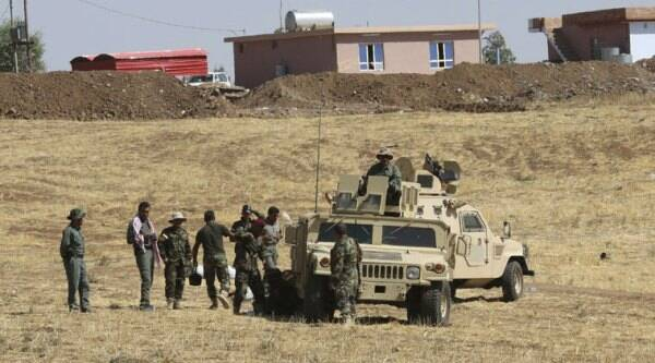 Kurdish peshmerga forces stand by their armed vehicles in Mahmoudiyah, Iraq, a day after they take control of the village from the Islamic State group, as they patrol on Wednesday, Oct. 1, 2014. (Source: AP)