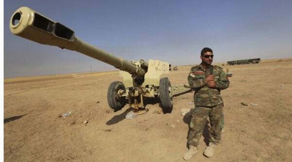 A Kurdish peshmerga fighter stands next to a firearm in Mahmoudiyah, Iraq, where fighters took control of it from the Islamic State group on Tuesday, while patrolling in the northern village on Wednesday, Oct. 1, 2014. (Source: AP)