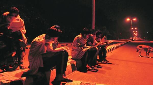 Students study under streetlights. (Source:Express photo by Gurmeet Singh)