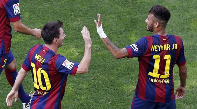 Lionel Messi (L) is congratulated by teammate Neymar after scoring a goal against Rayo Vallecano. (Source: Reuters)