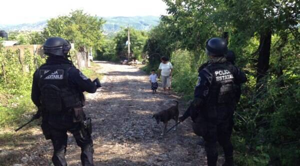 State police guard the road leading to the site where an alleged clandestine grave was found near the town of Pueblo Viejo, Mexico, Saturday, Oct. 4, 2014. (Source: AP)