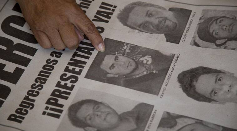 In this Thursday, Oct. 16, 2014 photo Maria Guadalupe Orozco points to the image of her missing son Francis Garcia Orozco on a leaflet of missing persons, during an interview with the Associated Press in Iguala, Mexico. (Source: AP)