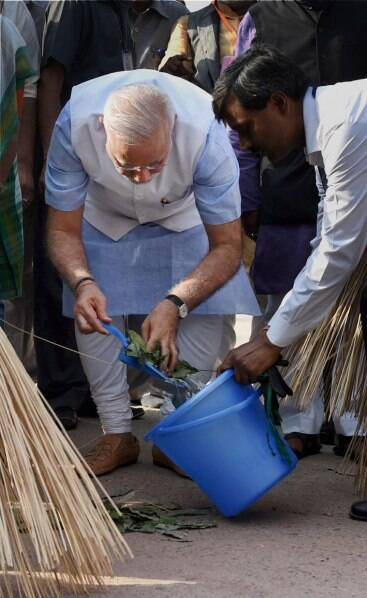 Prime Minister Narendra Modi dumps the garbage into a bin during the launch of 'Swachh Bharat Abhiyan' in Valmiki Basti in New Delhi on Thursday. (Source: PTI)