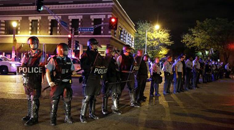 Police wearing riot gear form a line to contain protesters Thursday, Oct. 9, 2014, a day after Vonderrit D. Myers was shot and killed by white, off-duty St. Louis police officer in St. Louis. (Source: AP)