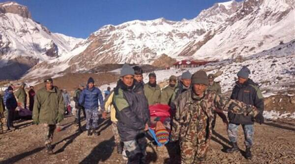 In this photo provided by the Nepalese army, soldiers carry an avalanche victim before he is airlifted in Thorong La pass area, Nepal, Wednesday, October 15, 2014.