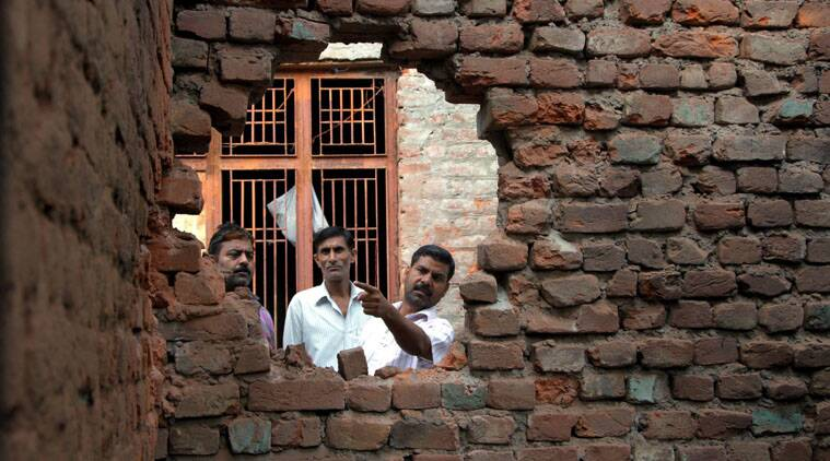 A villager shows the damaged wall of his house after firing from the Pakistani side at Arnia sector in Jammu. (Source: PTI)