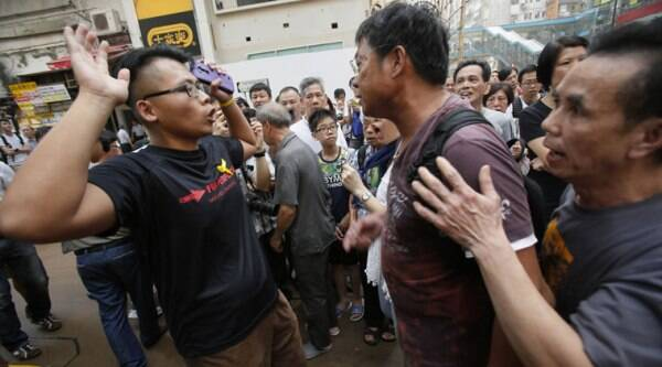 A pro-democracy student protester, left, argues with angry locals trying to remove the barricades blocking local streets in Causeway Bay, Hong Kong on Friday. (Source: AP photo)