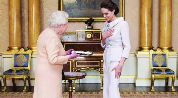 Actress Angelina Jolie is presented with the Insignia of an Honorary Dame Grand Cross of the Most Distinguished Order of St Michael and St George, by Britain's Queen Elizabeth in the 1844 room at Buckingham Palace in London on October 10