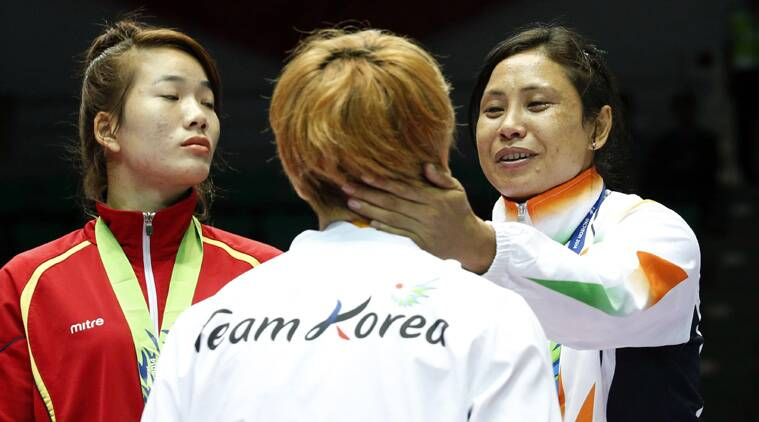 Laishram Sarita Devi (R) talks with South Korea's silver medallist Park Ji-na during the medal ceremony. (Source: Reuters)