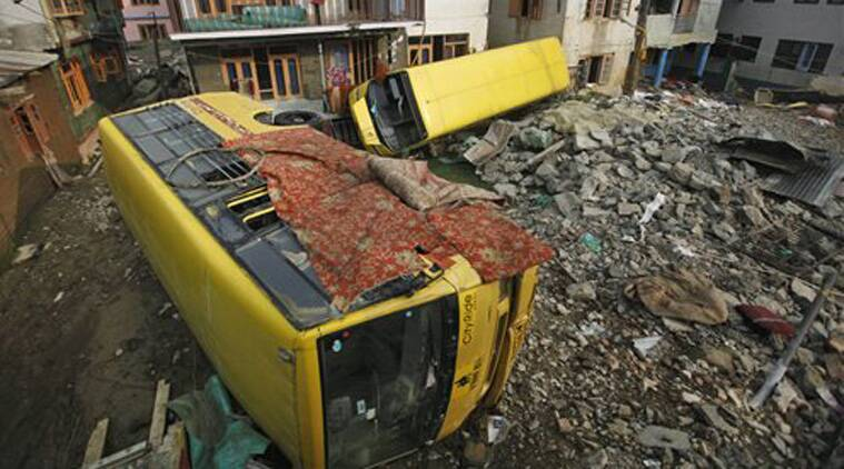 In this Wednesday, Oct. 1, 2014 photo, school buses washed away by severe flooding lie inside the compound of a residential house in Srinagar, India. (Source: PTI)
