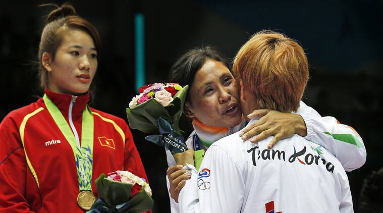 Sarita refused to wear the medal when it was presented on Wednesday and draped it over the South Korean fighter who had beaten her the previous day. (Source: AP)