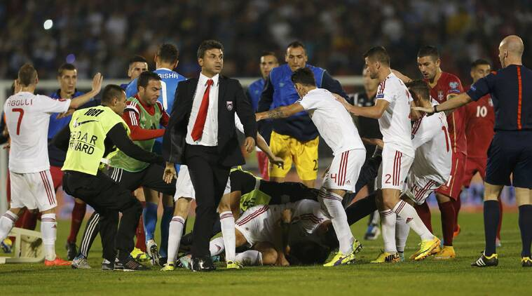 Serbian fans find their way to the pitch and try to attack  Albanian players as things quickly go out of control