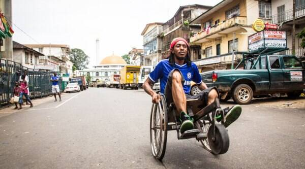 A man travels along a street in his wheelchair during a three-day lockdown to prevent the spread on the Ebola virus in Freetown, Sierra Leone, Sunday, Sept. 21, 2014. (Source: AP)