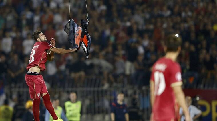 Serbia's Stefan Mitrovic  grabs the 'Greater  Albania' flag and attemps to crush it in the 41st minute of the game