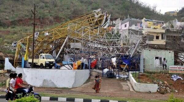 People watch damage to a property after Hudhud Cyclone in Vishakapatnam on Monday. (Source: PTI Photo)