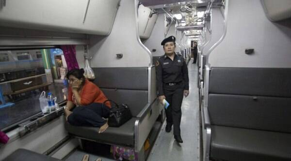In this Sept. 22, 2014 photo, a female railway police officer patrols in a train carriage for women and children, at Hua Lamphong train station in Bangkok, Thailand. (Source: AP)