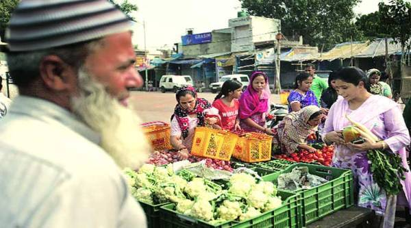 People buy vegetables from a government stall in Trilokpuri on Tuesday.