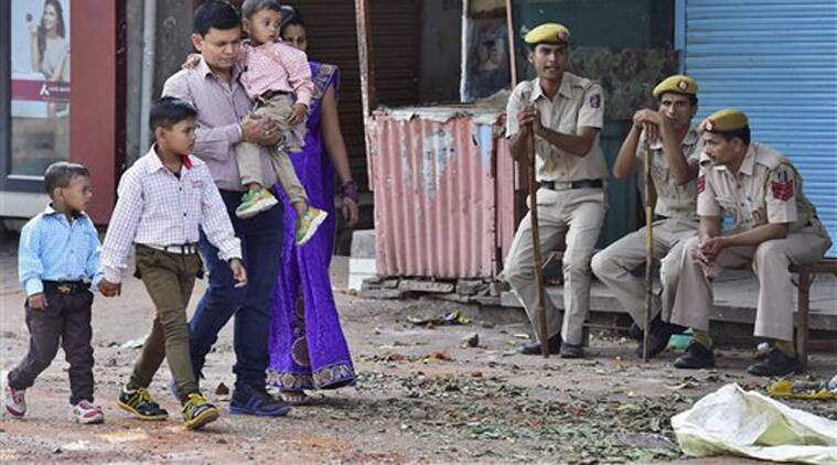A family walks past policemen guarding an area of curfew bound Trilokpur. (Source: PTI)