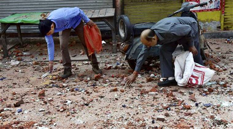 Policemen collect evidence from a road filled with brick bats in Trilokpuri, New Delhi on Sunday, two days after a clash between two groups. (Source: PTI)
