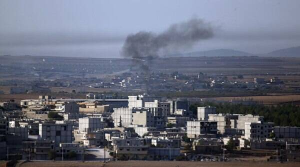 Smoke from a fire rises following a strike in Kobani, Syria, during fighting between Syrian Kurds and the militants of Islamic State group. (Source: AP photo)
