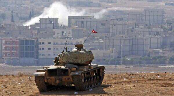 Turkish soldiers in a a tank hold their position on a hilltop at the Turkey-Syria border, overlooking smoke rising from a strike in Kobani, Syria, during fighting between Syrian Kurds and the militants of Islamic State group, on Thursday. (Source: AP photo)