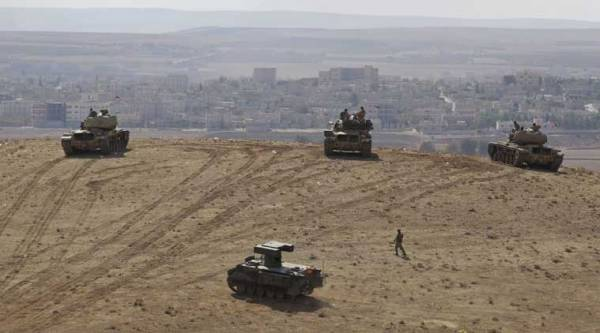 Turkish soldiers in tanks and an armored vehicle hold their positions on a hilltop in the outskirts of Suruc, at the Turkey-Syria border, overlooking the Kobani town, Syria, during fighting between Syrian Kurds and the militants of Islamic State group on Thursday, Oct. 9, 2014. (Source: AP)