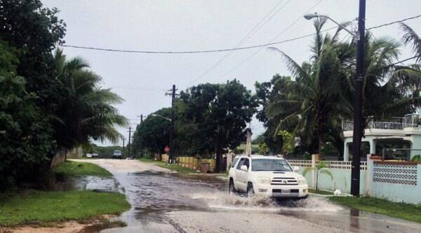 A vehicle drives through a flooded street in the Dededo village of Guam, Monday, Oct. 6, 2014. A typhoon whipped the Mariana Islands, including Guam, with high winds and heavy rain. As conditions improved, Guam officials shut down the island's storm center, the airport resumed full operations, and government agencies and many businesses began reopening. (Source: AP)