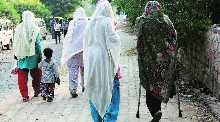 Wife and little daughter (left) of Usman, one of the rapists, outside the court on Monday. To their right are Usman's mother and relatives of other convicts. (Source: Express photo by Renuka Puri)