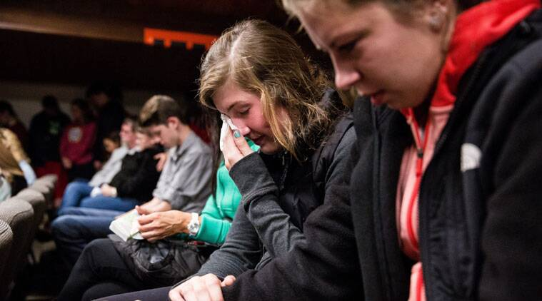 Friends comfort each other as hundreds packed into The Grove Church for a vigil in mourning of an earlier shooting at Marysville Pilchuck High School.