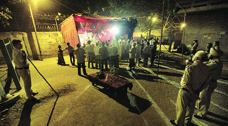 Policemen watch aarti at Mata ki chowki, the spot where a fight may have triggered Trilokpuri riots. (Source: Express photo by Ravi Kanojia)