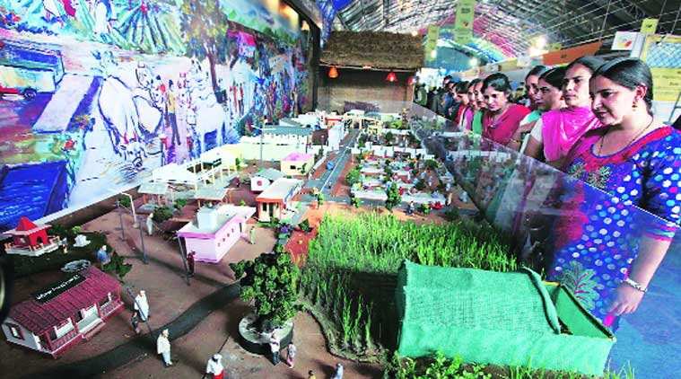 Visitors look at a model of a modern village at CII Agro Tech 2014 in Sector 17 Parade Ground on Saturday. (Source: Express photo by Kamleshwar Singh)