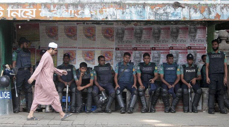 A man walks past Bangladeshi police officers sitting outside a special war crimes tribunal ahead of a verdict to be pronounced for Jamaat-e-Islami chief Motiur Rahman Nizami, in Dhaka, Bangladesh, Wednesday, Oct. 29, 2014.  (Source: AP)