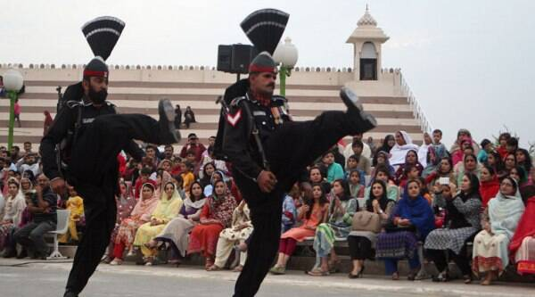 Pakistani border guards perform high kicks during a flag lowering ceremony after a Sunday suicide bombing at the Pakistan-Indian border post, in Wagah. (Source: AP photo)