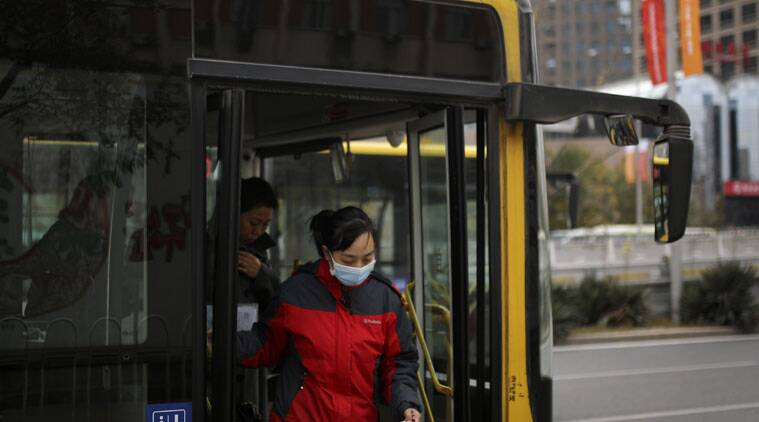 A woman wearing a mask walks out from a bus at the Central Business District in Beijing, China Tuesday, Nov. 11, 2014. All the sky-clearing measures plus cooperation from the weather kept Beijing relatively free of air pollution for most of a seven-day Asia-Pacific conference ending Tuesday. Then, toward the end as top leaders met, the smog crept back. (Source: AP)