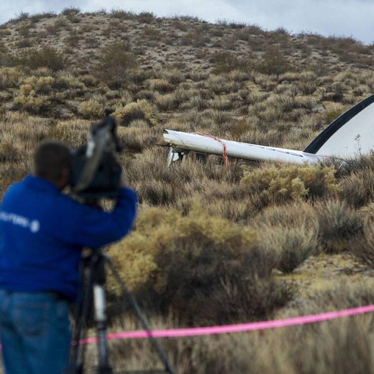 A journalist makes a video of the wreckage near the site where a Virgin Galactic space tourism rocket, SpaceShipTwo, exploded and crashed in Mojave, Calif. (Source: AP)