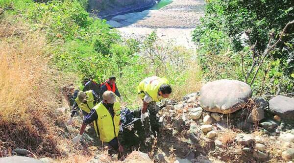 Rescuers carry what police claimed was the woman's body. (Source: Express photo)