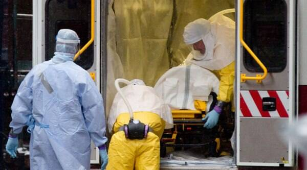 Health workers in protective suits unload Dr. Martin Salia, a surgeon working in Sierra Leone who had been diagnosed with Ebola, from an ambulance at the Nebraska Medical Center in Omaha on Nov. 15. (Source: AP photo)