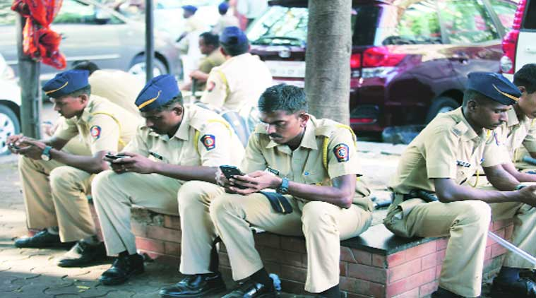 Policemen on bandobast duty check their cellphones. (Source: Express photo by Vasant Prabhu)