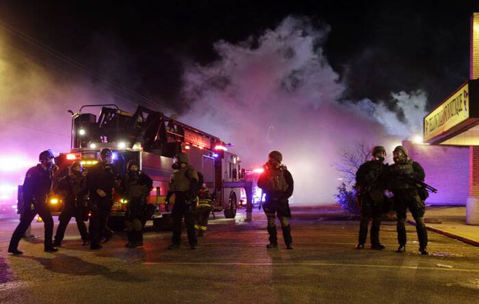 Smoke fills the streets as some buildings are on fire after the announcement of the grand jury decision Monday, Nov. 24, 2014, in Ferguson, Mo. (Source: AP)