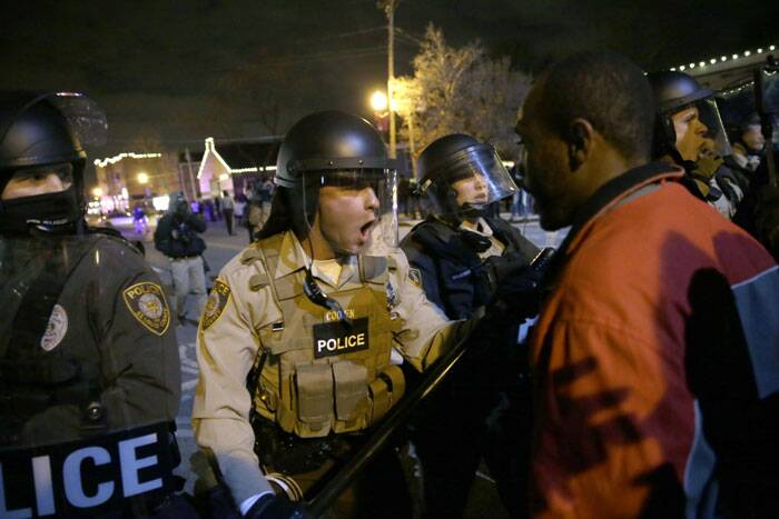 Police officers confront protesters after the announcement of the grand jury decision not to indict police officer Darren Wilson in the fatal shooting of Michael Brown, an unarmed black 18-year-old, Monday, Nov. 24, 2014, in Ferguson, Mo. (Source: AP)