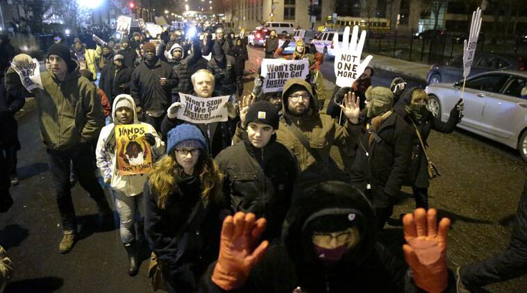 Protesters march during a rally near the Chicago Police headquarters after the announcement of the grand jury decision not to indict Ferguson police officer Darren Wilson in the fatal shooting of Michael Brown, an unarmed black 18-year old, Monday, Nov. 24, 2014, in Chicago. (Source: AP)