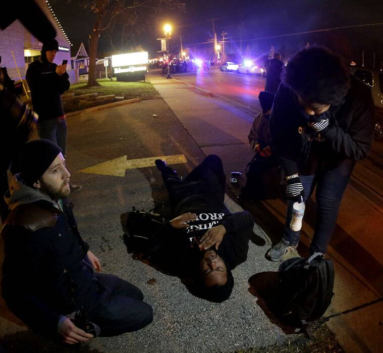 A man tries to catch his breath after police used tear gas to clear protesters from the street in front of the Ferguson Police Department (Source: AP)
