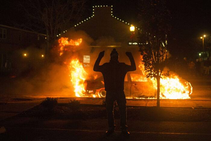 A man raises his arms in front of a burning police vehicle after a grand jury returned no indictment in the shooting of Michael Brown in Ferguson, Missouri, November 24, 2014. Gunshots were heard and bottles were thrown as anger rippled through a crowd outside the Ferguson Police Department in suburban St. Louis after authorities on Monday announced that a grand jury voted not to indict a white officer in the August shooting death of an unarmed black teen. (Source: Reuters)