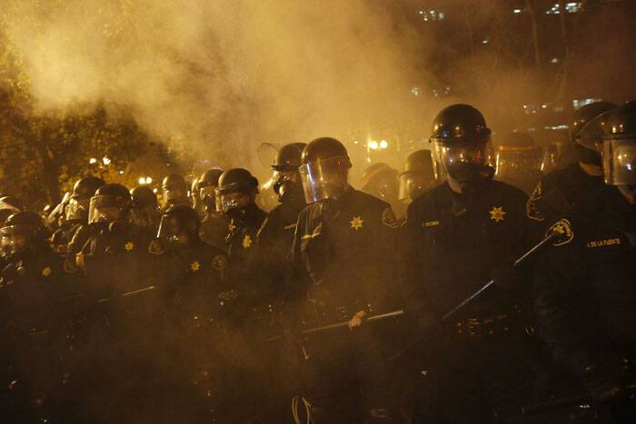 Police officers advance on demonstrators during a demonstration following the grand jury decision in the Ferguson, Missouri shooting of Michael Brown, in Oakland, California November 25, 2014. The grand jury decided on Monday not to indict a white police officer over the fatal August shooting of an unarmed black teenager. (Source: Reuters)