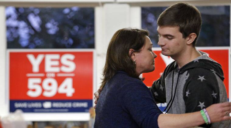Nicole Hockley, left, is embraced by campaign worker Jordan Fuzie after Hockley spoke to volunteers at a phone bank in support of Washington's Initiative 594, a measure seeking universal background checks on gun sales and transfers.