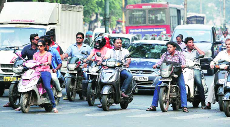 Two-wheeler riders not wearing helmets despite a traffic police drive was a common sight on the city roads on Saturday. (Source: Express photo by Sandeep Daundkar)