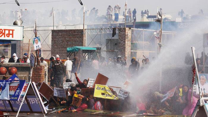 Supporters try to resist police water cannon as police storm the ashram of controversial guru Sant Rampal. (Source: PTI photo)
