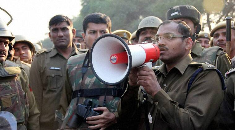Hisar: A police officer makes an announcement near the Satlok Ashram for the arrest of Sant Rampal in Hisar on Monday. (Source: PTI)